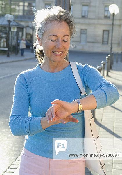 Ältere Frau sieht auf Straße auf Armbanduhr