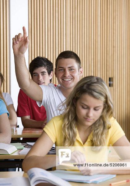 Schüler meldet sich in Klassenzimmer