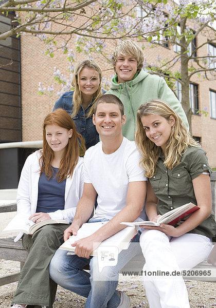 Fünf Schülerinnen und Schüler sitzen auf Bank
