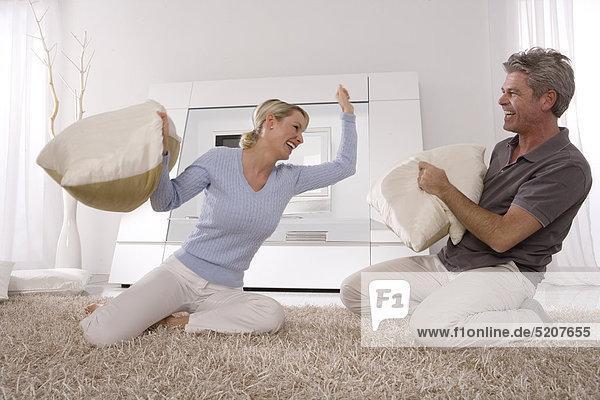 Paar im Wohnzimmer bei Kissenschlacht auf dem Teppich