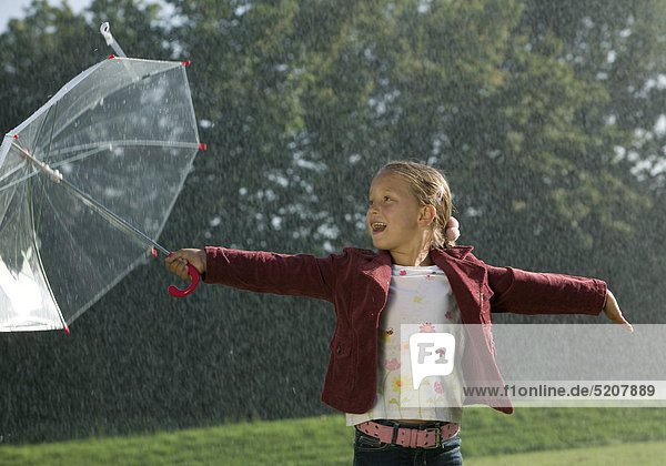 Kleines Mädchen steht mit Regenschirm im Regen  lacht Kleines Mädchen steht mit Regenschirm im Regen, lacht