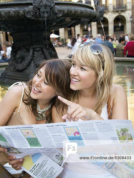 Zwei junge Frauen mit Stadtplan in Barcelona Zwei junge Frauen mit Stadtplan in Barcelona