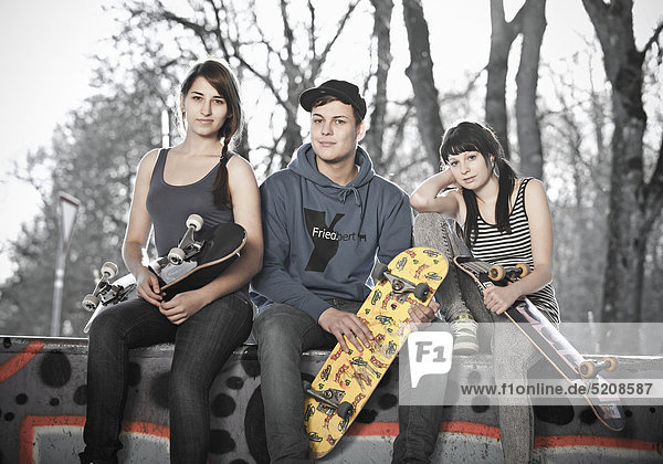 Drei Jugendliche mit Skateboards