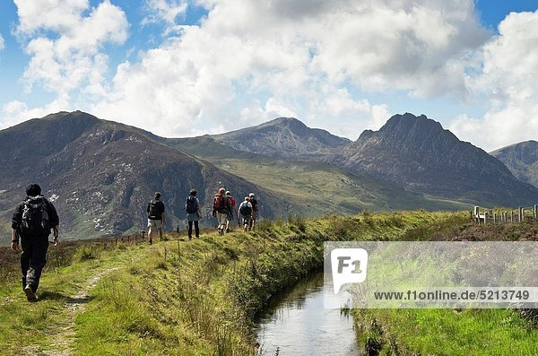 Ogwen  Conwy North Wales  UK  Europe Ramblers group walking along a watercourse with view along the Ogwen valley to Tryfan and the Glyders in Snowdonia National Park