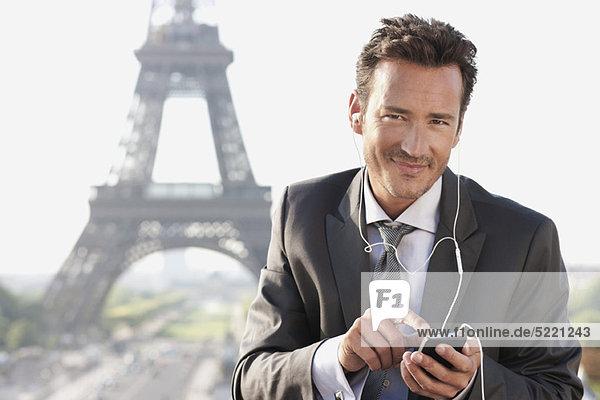 Geschäftsmann mit Handy und Eiffelturm im Hintergrund  Paris  Ile-de-France  Frankreich