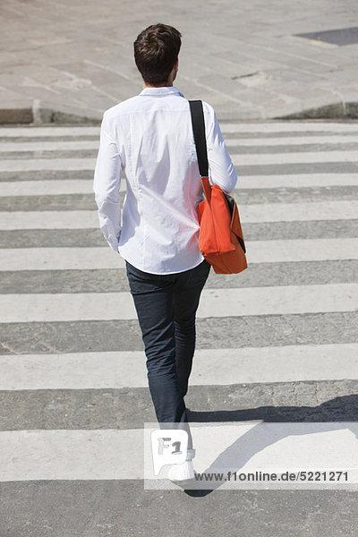 Rückansicht eines Mannes  der im Zebrastreifen läuft  Paris  Ile-de-France  Frankreich