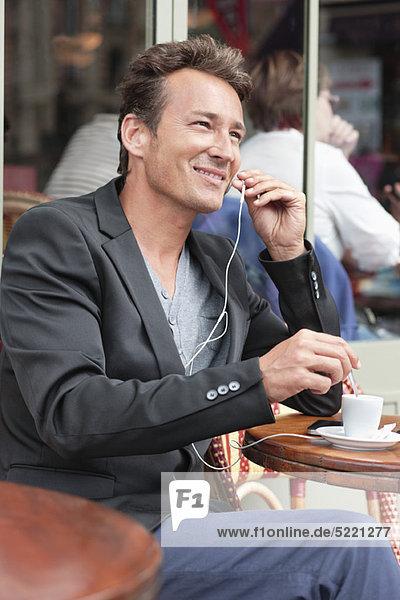 Man talking on a mobile phone in a restaurant  Paris  Ile-de-France  France