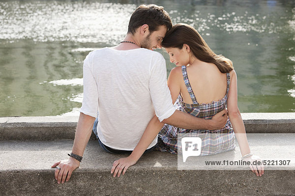 Rear view of a couple sitting at the ledge of a canal  Paris  Ile-de-France  France