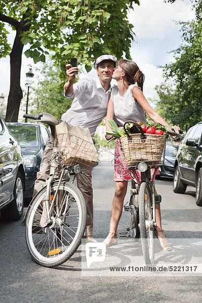 Fahrradfahren und Fotografieren mit dem Handy  Paris  Ile-de-France  Frankreich