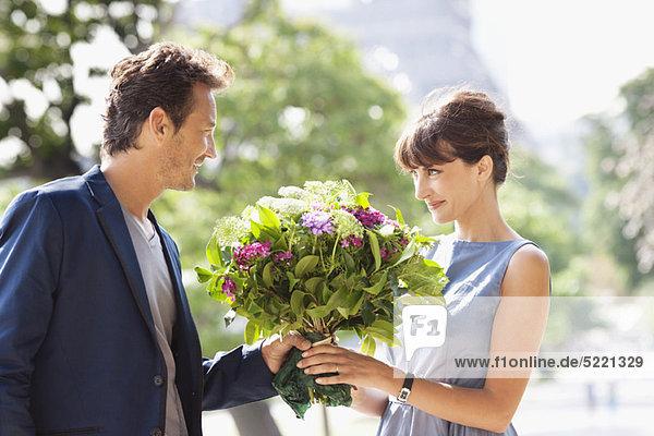 Mann schenkt einer Frau einen Blumenstrauß mit dem Eiffelturm im Hintergrund  Paris  Ile-de-France  Frankreich