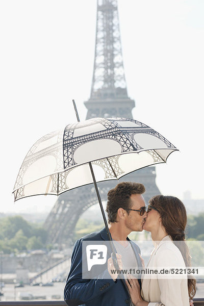 Couple kissing under an umbrella with the Eiffel Tower in the background  Paris  Ile-de-France  France