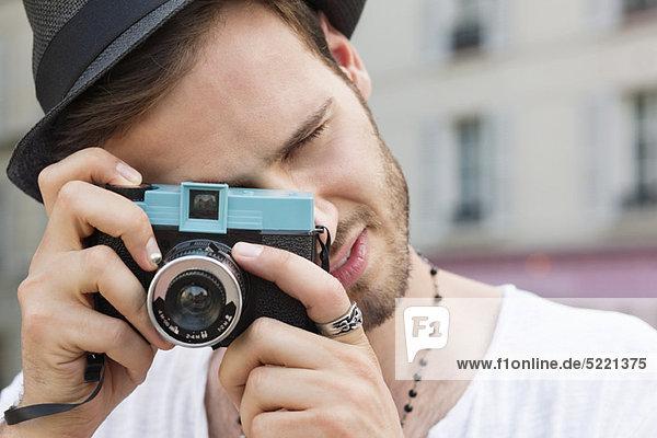 Man photographing with a camera,  Paris,  Ile-de-France,  France