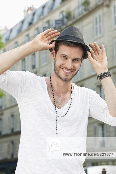 Porträt eines Mannes  der seinen Hut anpasst  Paris  Ile-de-France  Frankreich