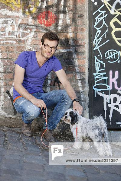 Mann mit einem Welpen vor einer Graffiti-Wand  Paris  Ile-de-France  Frankreich