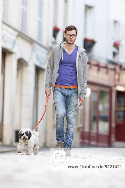 Mann mit einem Hund an der Leine auf der Straße  Paris  Ile-de-France  Frankreich