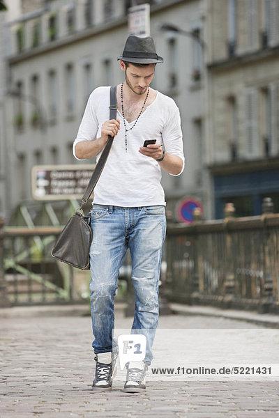Mann unterwegs und SMS mit dem Handy  Paris  Ile-de-France  Frankreich