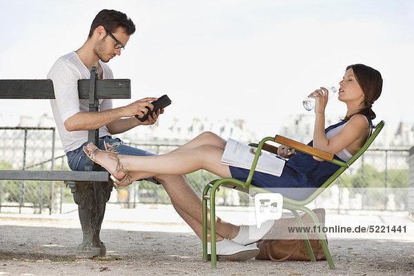 Frau trinkt Wasser und ihr Mann mit einem digitalen Tablett  Jardin des Tuileries  Paris  Ile-de-France  Frankreich