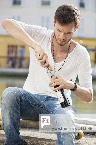 Mann beim Öffnen einer Weinflasche mit Korkenzieher  Paris  Ile-de-France  Frankreich