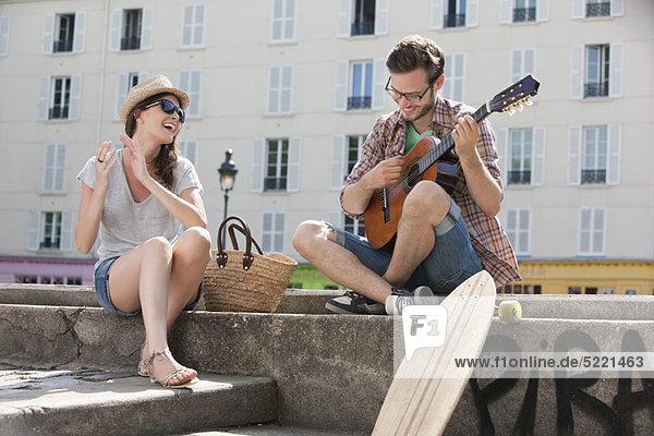 Mann spielt Gitarre mit klatschender und lächelnder Frau  Canal St Martin  Paris  Ile-de-France  Frankreich