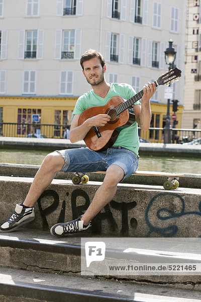 Mann spielt Gitarre  Canal St Martin  Paris  Ile-de-France  Frankreich