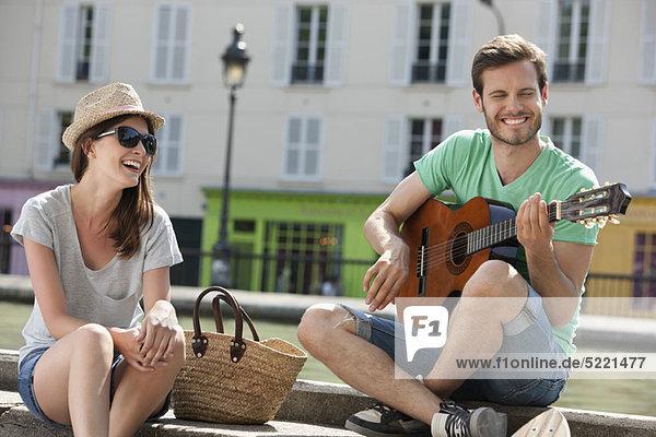Mann spielt Gitarre mit einer lächelnden Frau  Canal St Martin  Paris  Ile-de-France  Frankreich