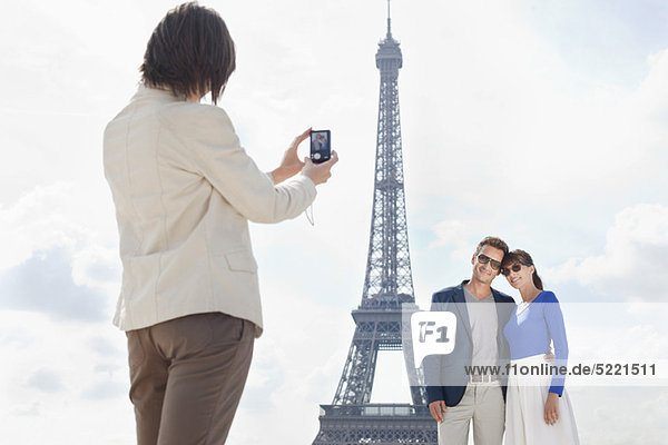 Woman taking a picture of couple with the Eiffel Tower in the background  Paris  Ile-de-France  France