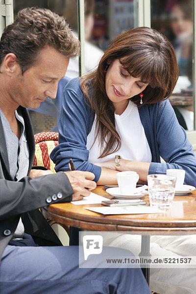 Frau schaut auf einen Mann  der in einem Restaurant unterschreibt  Paris  Ile-de-France  Frankreich