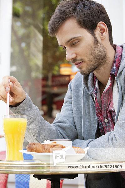 Mann  der an einem Straßencafé sitzt und nachdenkt  Paris  Ile-de-France  Frankreich