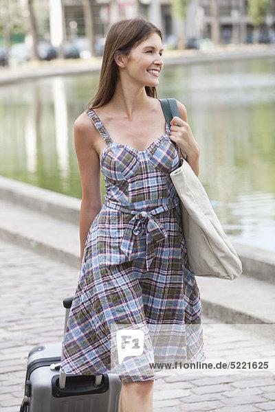 Woman pulling a suitcase and smiling  Paris  Ile-de-France  France