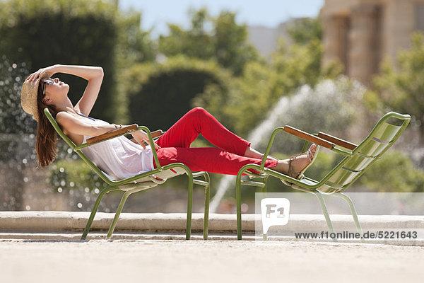 Woman resting in a chair near a pond  Bassin octogonal  Jardin des Tuileries  Paris  Ile-de-France  France