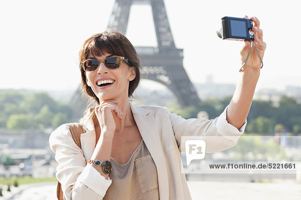 Frau beim Fotografieren mit dem Eiffelturm im Hintergrund  Paris  Ile-de-France  Frankreich