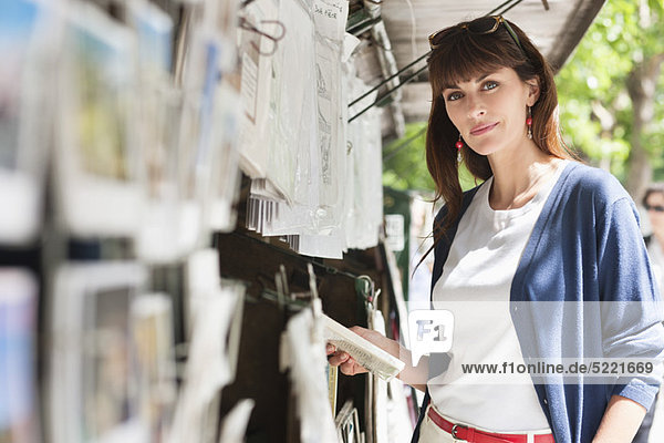Woman holding a book at a book stall  Paris  Ile-de-France  France