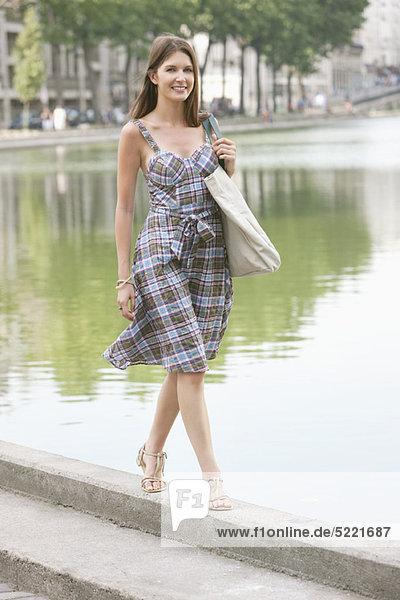 Woman walking on the ledge of a canal  Paris  Ile-de-France  France