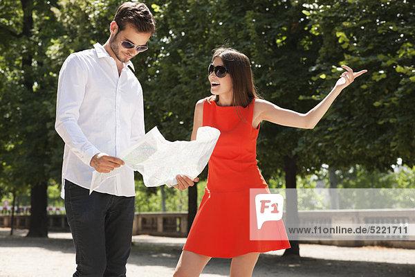 Mann beim Lesen einer Karte mit einer Frau  Terrasse De l'Orangerie  Jardin des Tuileries  Paris  Ile-de-France  Frankreich