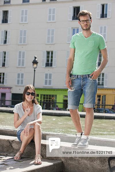 Paar auf einem Felsvorsprung eines Kanals  Canal St Martin  Paris  Ile-de-France  Frankreich