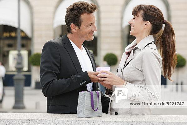 Frau schenkt einem Mann  Paris  Ile-de-France  Frankreich