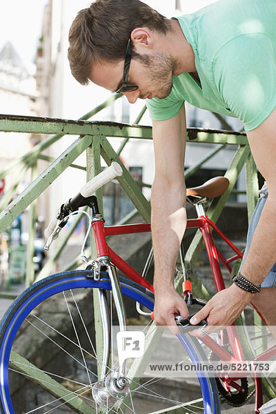 Mann schließt sein Fahrrad ab  Paris  Ile-de-France  Frankreich