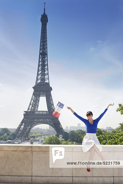 Woman holding a French flag sitting on a stone wall with the Eiffel Tower in the background  Paris  Ile-de-France  France
