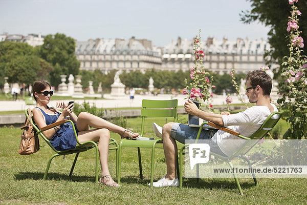 Mann mit einem Laptop und einer Frau auf dem Handy  Jardin des Tuileries  Paris  Ile-de-France  Frankreich