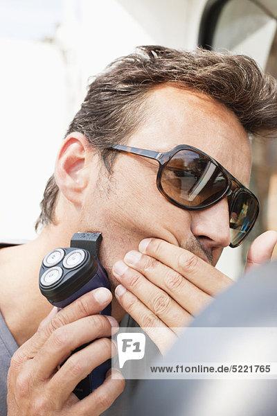 Man using an electric shaver on his face  Paris  Ile-de-France  France