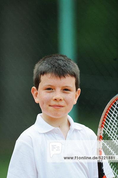 Porträt der jungen Boy Holding Tennisschläger