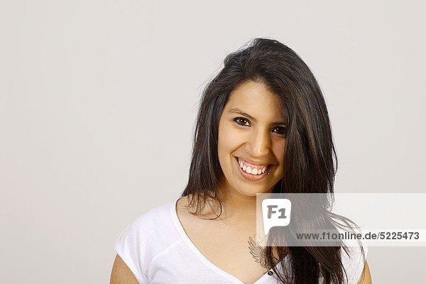 Studio shot of young Chilean woman  smiling