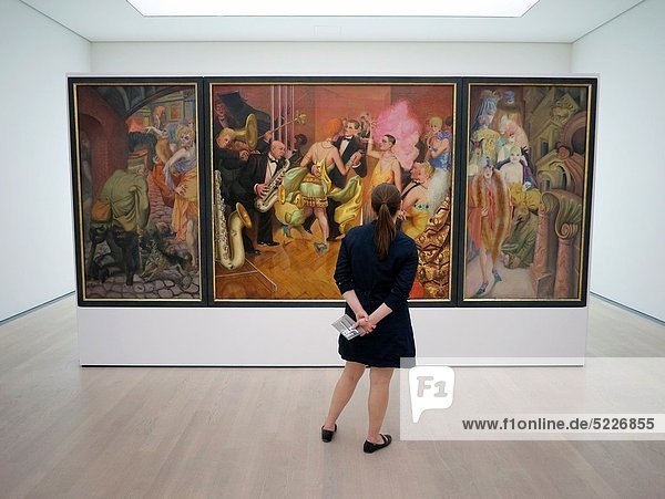 Woman looking at painting Grossstadt by Otto Dix at interior of Kunstmuseum in Stuttgart Germany