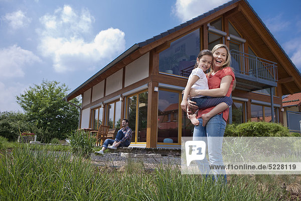 Family in front of Lehner energy house  Poing  Bavaria  Germany  Europe