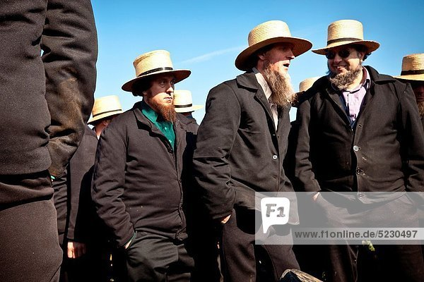 Amish men bid on farm equipment during the Annual Mud Sale to support the Fire Department in Gordonville  PA
