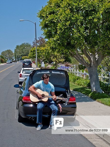 Sitting on the rear of his car under a sunny blue sky  a young man practices his guitar on a sunny suburban street in Laguna Niguel  California
