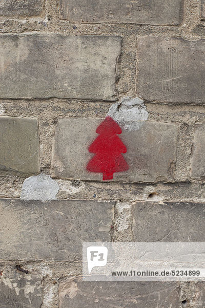 Ein roter Weihnachtsbaum auf einer Ziegelmauer