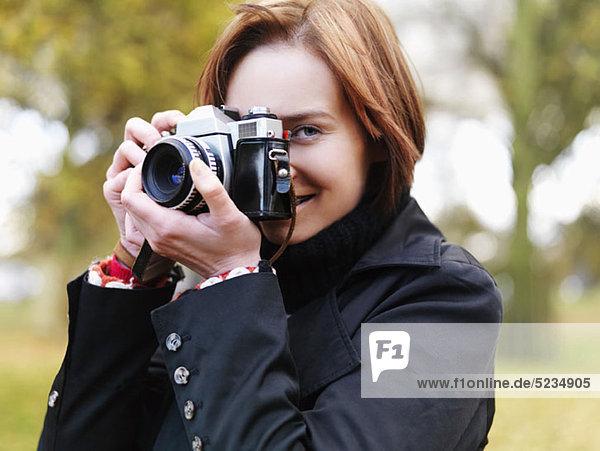 Eine Frau  die sich auf ein Foto vorbereitet  im Freien  mit Kopf und Schultern.