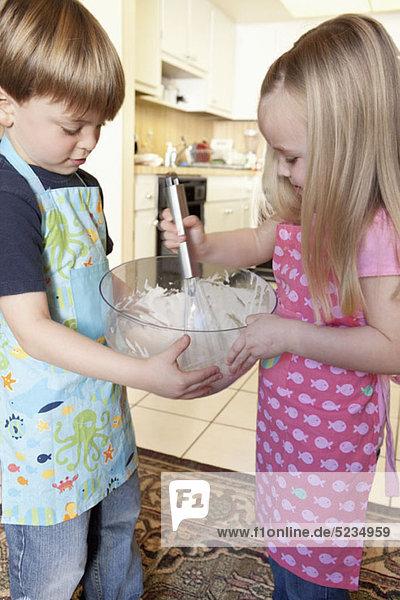 Ein Junge und ein Mädchen mischen Zutaten in einer Schüssel.