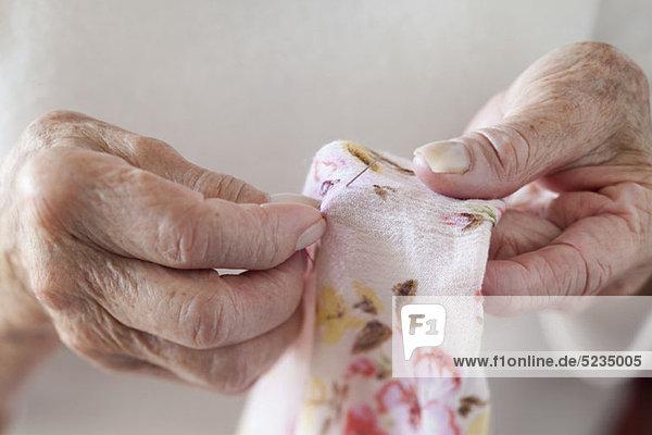Detail eines Senioren-Frauen-Stickerei-Stoffes